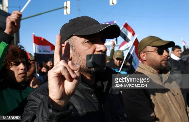 CORRECTION An Iraqi man with duct tape across his mouth takes part in a silent protest of mostly supporters of prominent cleric Moqtada Sadr on...