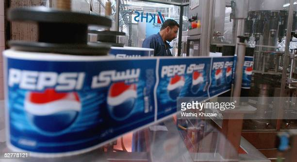 An Iraqi man works at the Baghdad Soft Drinks Company on May 9 2005 in Baghdad Iraq Violence and taxfree imported goods have affected Iraqs industry...