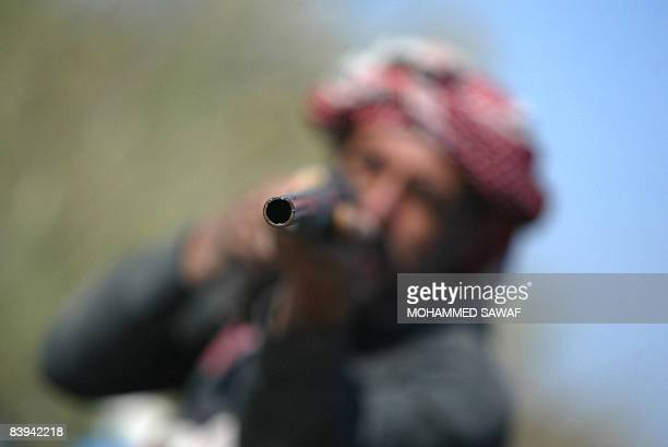 An Iraqi Marsh Arab points his rifles as he hunts for birds in the reeds along the shores of Hor Hamidi 30 kms south of the Souk akShuykh 420 kms...