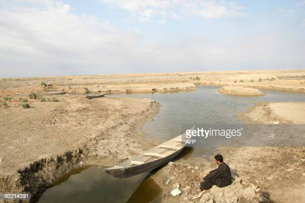 An Iraqi marsh Arab sits looking out at the barren and dried out Hor or marshes some 130 km southwest of the southern city of Basra on November 18...