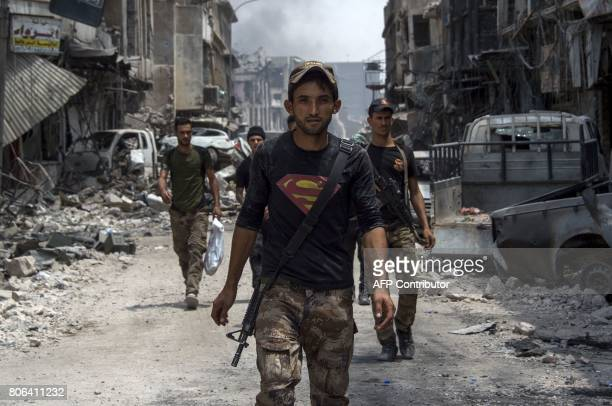 TOPSHOT An Iraqi member of the CounterTerrorism Services wearing a superman Tshirt walks in the Old City of Mosul on July 3 2017 during an ongoing...