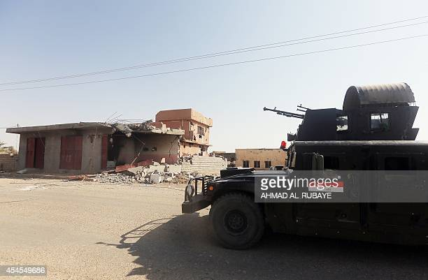 An Iraqi military truck drives past destroyed buildings from fighting with Islamic State militants on a road outside of Tikrit on September 3 2014...