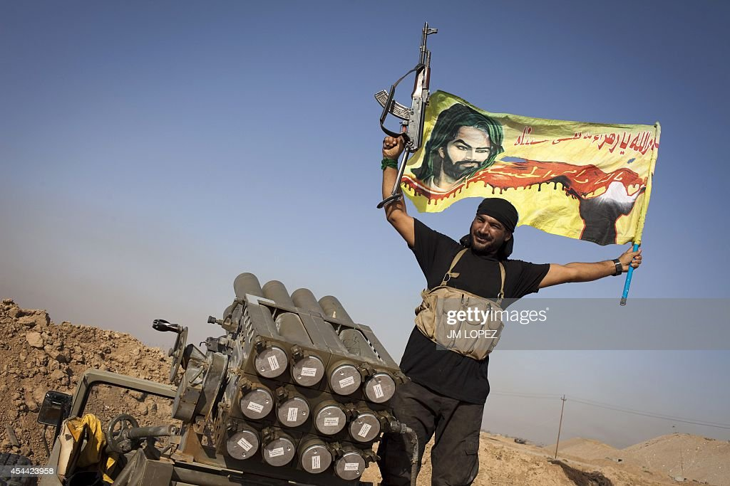 An Iraqi militia fighter from Shiite cleric Moqtada alSadr's Saraya alSalam waves a flag next to a rocket launcher during heavy clashes with Islamic...