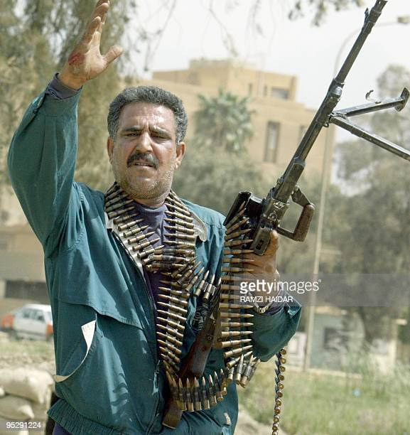 An Iraqi militiaman gestures in a Baghdad street 05 April 2003 About 1000 Iraqi troops were killed in fierce fighting today during a move by US tanks...