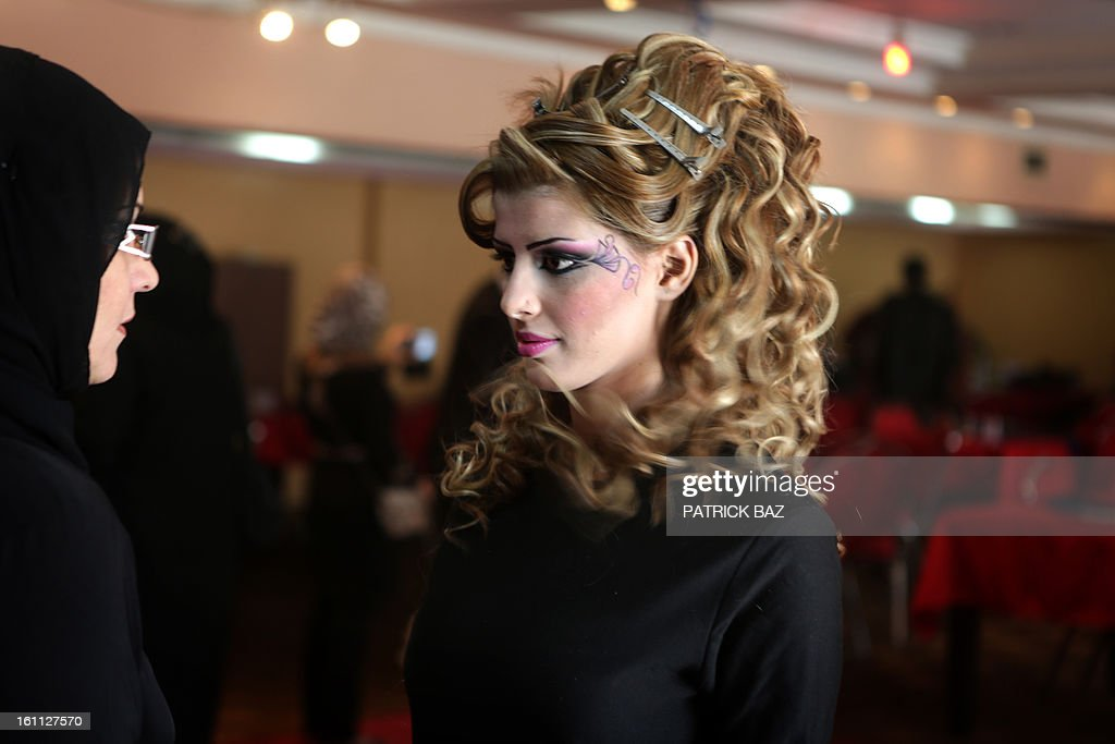 An Iraqi model is being briefed on how to walk on the catwalk before a show during a hairdressers and make up artists festival on February 9, 2013 in Baghdad. It is the first time that this kind of festival takes place in the Iraqi capital since 1999.