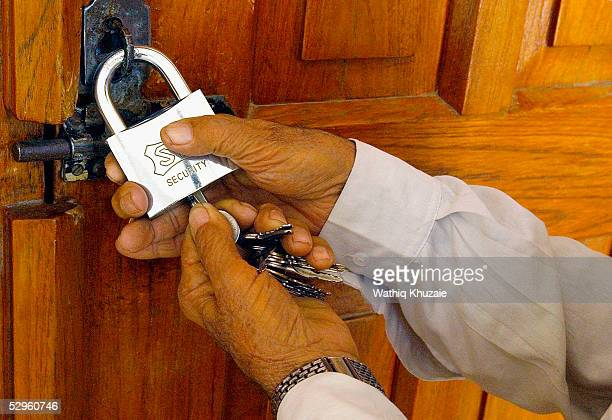 An Iraqi mosque caretaker locks the gate of alQazaz Sunni mosque May 21 2005 in Baghdad Iraq Sunnis clerics announced a closing of Sunni mosques...