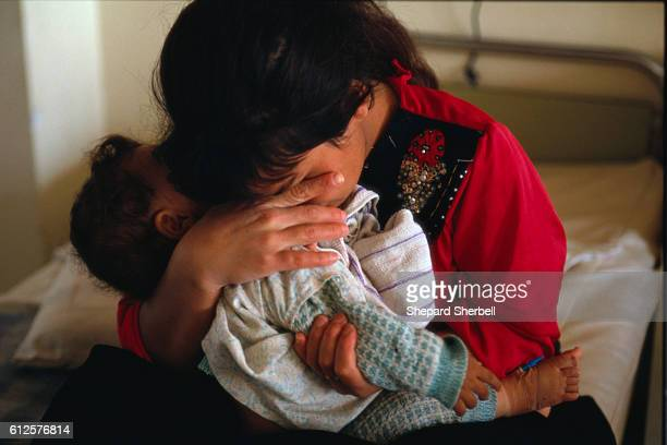 An Iraqi mother holds her baby and cries in a room at the Saddam Central Hospital for Children