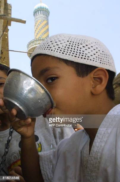 An Iraqi Muslim boy drinks water at a mosque in Baghdad 05 July 2002 before the weekly Friday prayers as temperatures soared to 47 degrees Celsius UN...