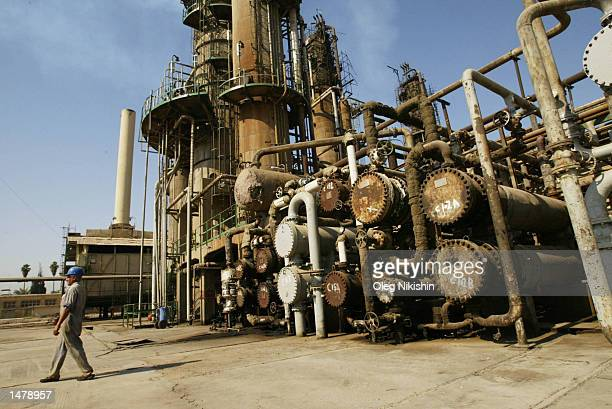 An Iraqi oil worker walks through the AlDoura oil refinery October 14 2002 in Baghdad Iraq US President George W Bush signed a congressional...