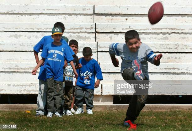 An Iraqi orphan kicks a football for the first time during a American football skills camp run by US soldiers September 27 2003 at the alTaleba...