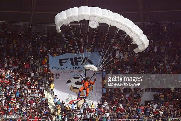 An Iraqi parachutist glides during a football match the Iraqi national team and the Karbala club to celebrate the opening of the new Karbala...