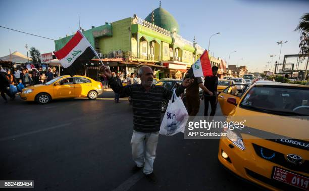 An Iraqi peddler sells Iraqi national flags amids traffic along a main street in the northern Iraqi city of Kirkuk on October 17 2017 Iraqi forces...