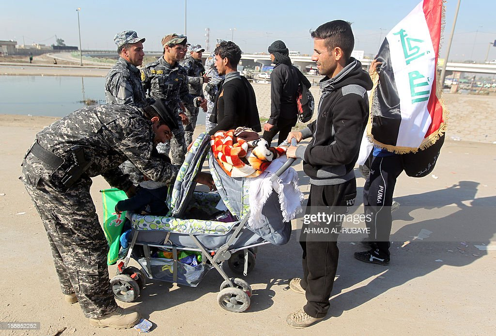 An Iraqi police officer searches a pram as Shiite Muslim pilgrims march along the main highway that links the Iraqi capital Baghdad with the central shrine city of Karbala on January 1, 2013, to take part in the Arbaeen religious festival which marks the 40th day after Ashura commemorating the seventh century killing of Prophet Mohammed's grandson, Imam Hussein. AFP PHOTO/AHMAD AL-RUBAYE