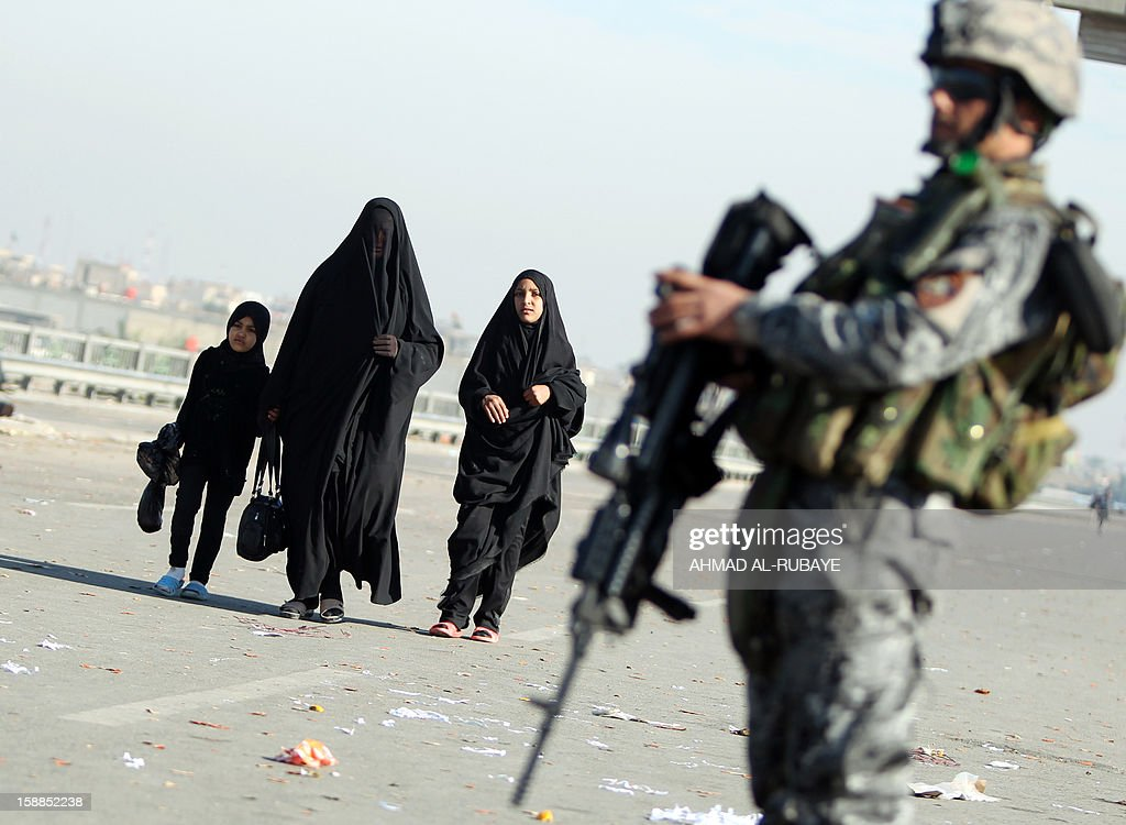 An Iraqi police officer stands guard as Shiite Muslim pilgrims march along the main highway that links the Iraqi capital Baghdad with the central shrine city of Karbala on January 1, 2013, to take part in the Arbaeen religious festival which marks the 40th day after Ashura commemorating the seventh century killing of Prophet Mohammed's grandson, Imam Hussein.