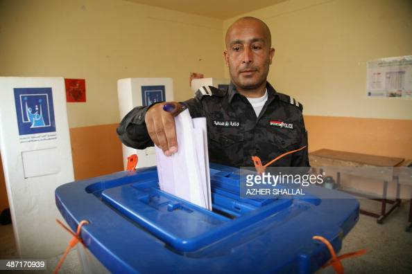 An Iraqi policeman casts his ballot at a polling station in the city of Ramadi west of the capital Baghdad on April 28 as members of the Iraqi...