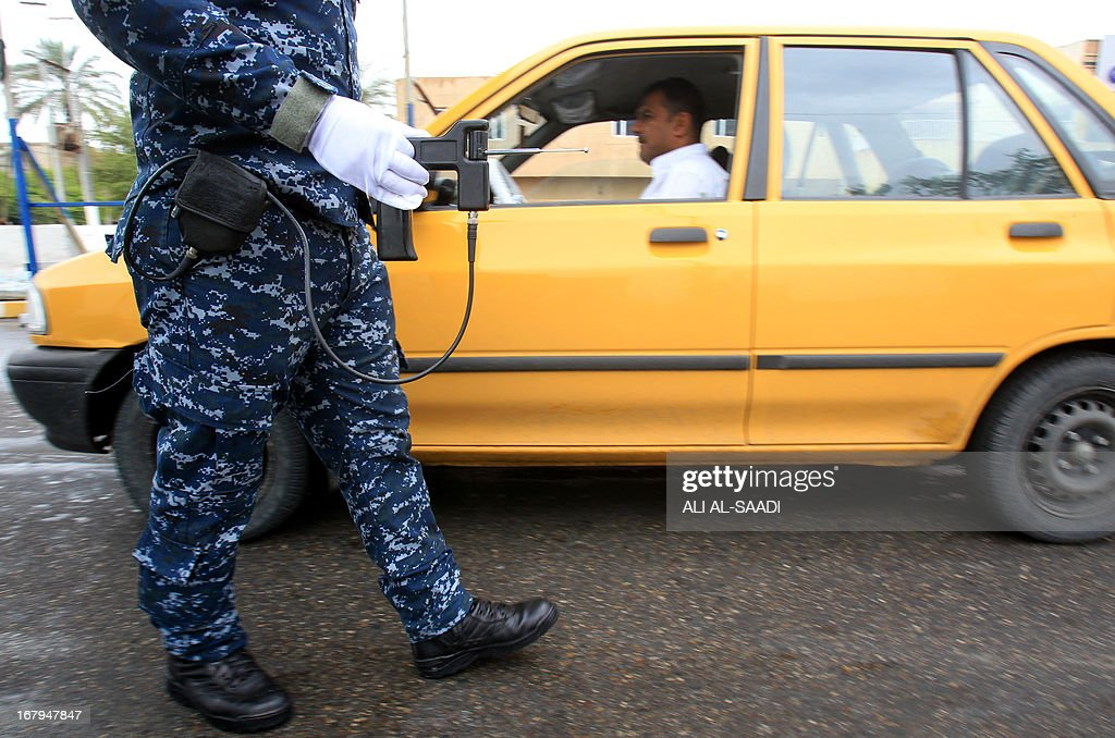 An Iraqi policeman checks a car using a fake explosive detecting device at a checkpoint in the al-Jadriyah district of Baghdad on May 3, 2013. A British businessman was sentenced to 10 years in jail for selling fake bomb detectors to the Iraqi government and other countries, by a judge who told him he had blood on his hands.