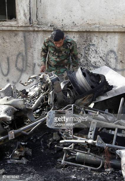 An Iraqi policeman checks the site of a blast which took place the previous day in the Iraqi capital Baghdad on April 29 2017 A car bomb attack on...
