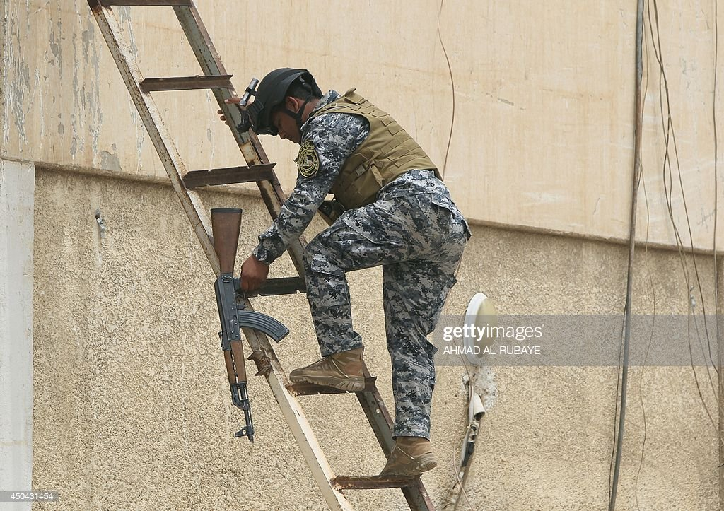 An Iraqi policeman climbs onto a roof of a military base in Baghdad, on June 11, 2014, after the parliament had received a joint request from Iraqi Prime Minister Nuri al-Maliki and the president's office to declare a state of emergency -- the procedure laid down in the constitution. Jihadists seized in the city of Mosul, Iraq's second and Nineveh province on June 10, in a major blow to the government apparently unable to halt the progress of armed.
