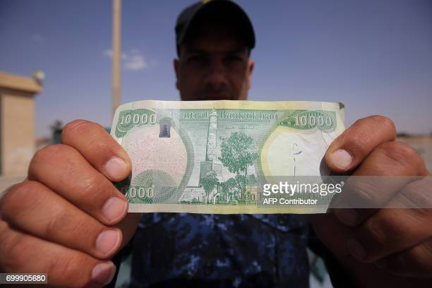 TOPSHOT An Iraqi policeman displays a 10000Iraqi dinar banknote bearing an image of Mosul's iconic leaning minaret known as the 'Hadba' on June 22 in...