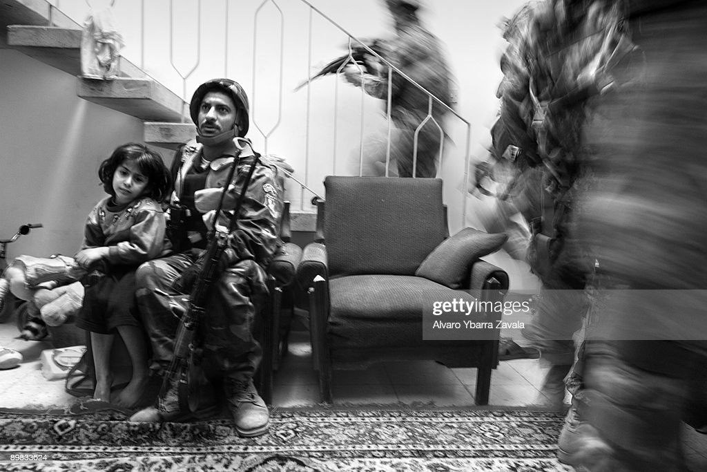 An Iraqi policeman holds onto a little girl during a house search by his Iraqi police unit in their own Karrada neighborhood in Baghdad, with Bravo Company, 2nd Platoon of the 1st Calvary Division, from Fort Hood, Texas.