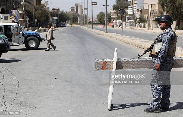 An Iraqi policeman mans a checkpoint on a street leading to the heavily fortified Green Zone in Baghdad on March 23 2012 Iraq tightened security...