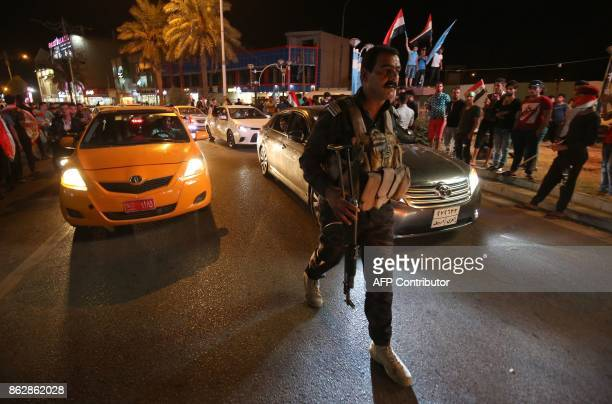 An Iraqi policeman monitors as Iraqis gather in the street in the city of Kirkuk to celebrate on October 18 after Iraqi government forces retook...