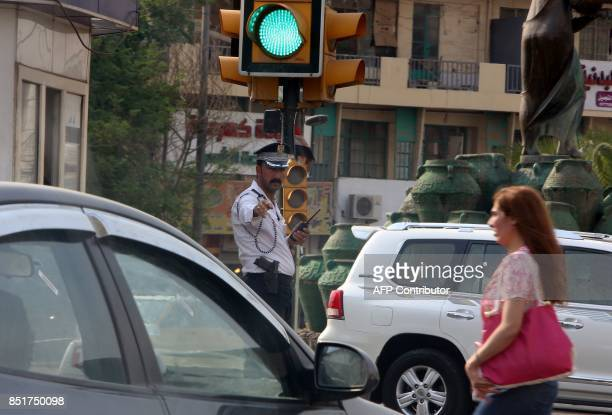 An Iraqi policeman stands in a street in the capital Baghdad on September 19 2017 The tradition in Iraq is for many cases to be settled by tribal...