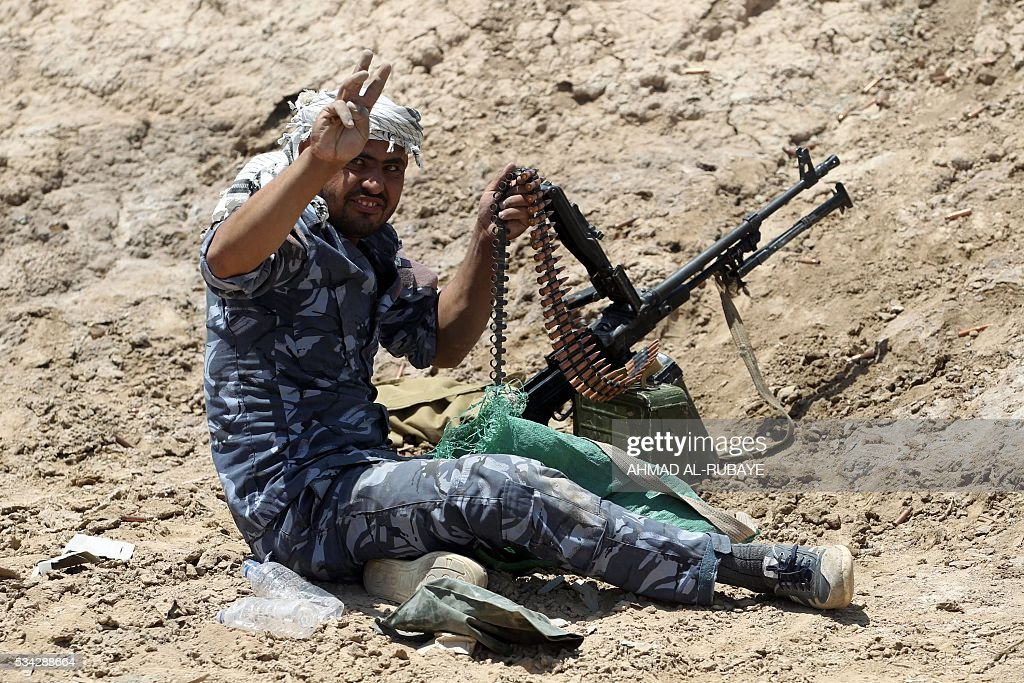 An Iraqi pro-government fighter flashes the V-sign as he holds a position near al-Sejar village, north-east of Fallujah, on May 25, 2016, as they take part in a major assault to retake the city from the Islamic State (IS) group. Iraqi forces, consisting of special forces, soldiers, police, paramilitary-fighters and pro-government tribesmen, launched a major assault to retake Fallujah, the scene of deadly battles during the US occupation and one of the toughest targets yet in Baghdad's war on the Islamic State group. / AFP / AHMAD