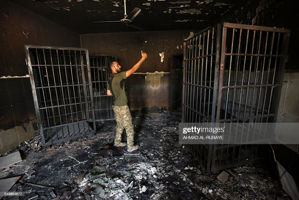 An Iraqi police forces member inspects a prison previously used by Islamic State (IS) group jihadists in the city of Fallujah on June 30, 2016 after the city was recaptured by government forces. Iraqi forces have retaken full control of Fallujah, a longtime jihadist bastion just 50 kilometres (30 miles) west of Baghdad, after a vast operation that was launched in May. / AFP / AHMAD