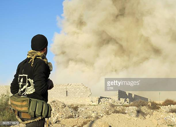 An Iraqi progovernment forces member watches smoke billowing in Ramadi's Hoz neighbourhood about 110 kilometers west of the capital Baghdad during...