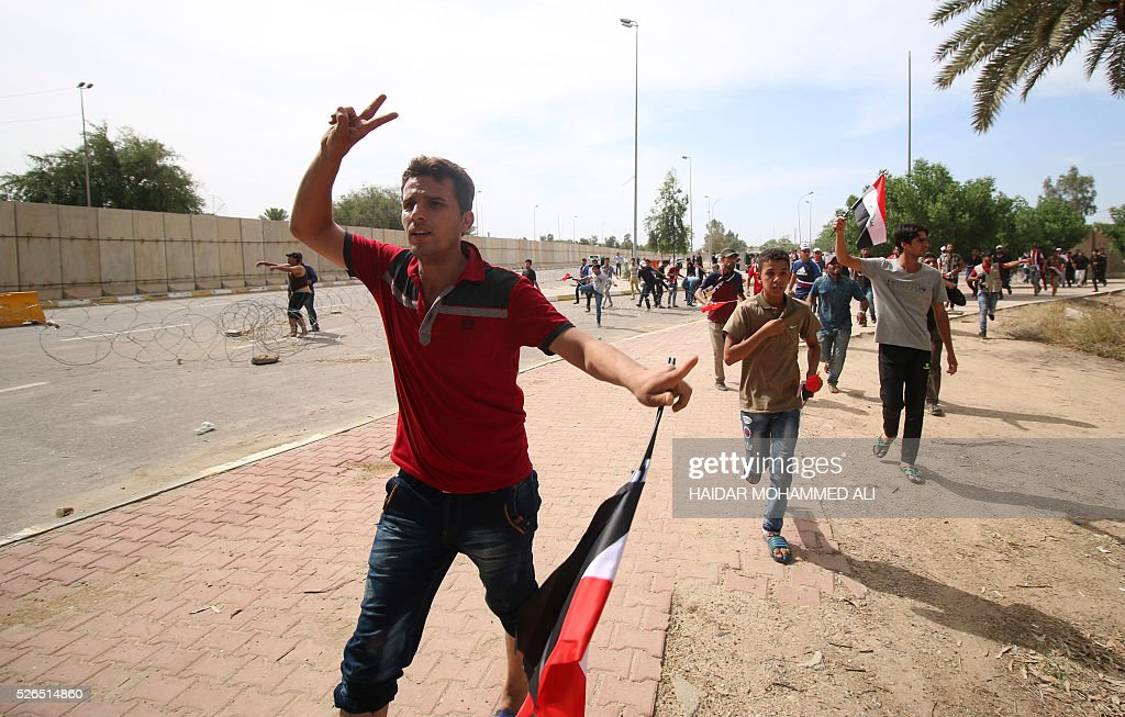 An Iraqi protester flashes the V-sign as he heads to the parliament after breaking into Baghdad's heavily fortified 'Green Zone' on April 30, 2016. Thousands of angry protesters broke into Baghdad's Green Zone and stormed the parliament building after lawmakers again failed to approve new ministers. Jubilant supporters of cleric Moqtada al-Sadr invaded the main session hall, shouting slogans glorifying their leader and claiming that they had rooted out corruption. / AFP / HAIDAR