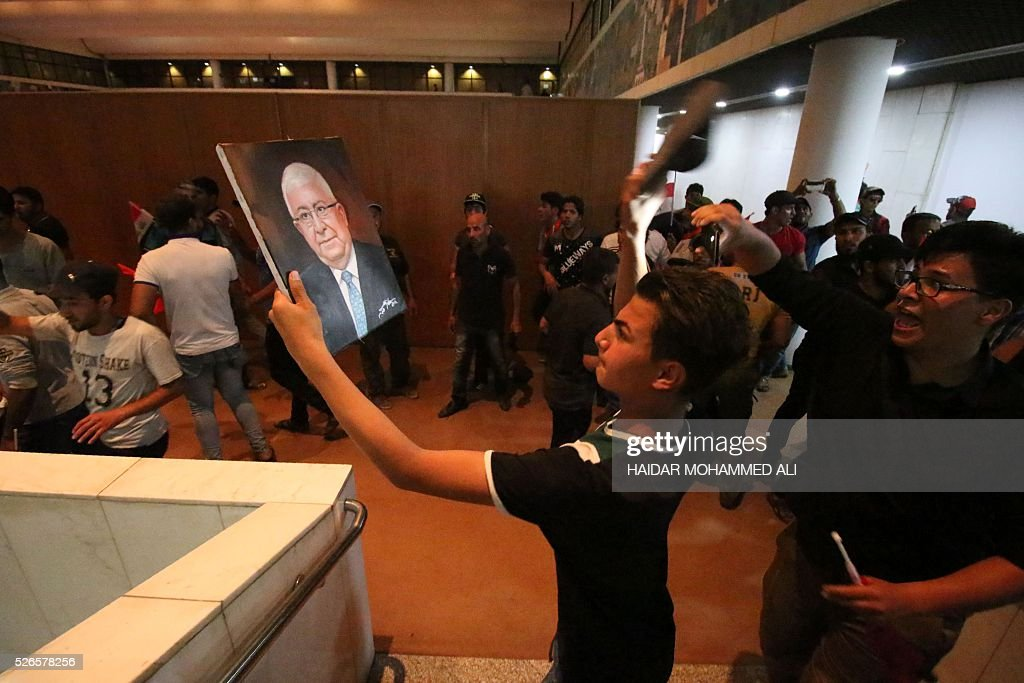 An Iraqi protester uses a shoe to hit a portrait of President Fuad Masum inside the parliament after breaking into Baghdad's heavily fortified 'Green Zone' on April 30, 2016. Thousands of angry protesters broke into Baghdad's Green Zone and stormed the parliament building after lawmakers again failed to approve new ministers. Jubilant supporters of cleric Moqtada al-Sadr invaded the main session hall, shouting slogans glorifying their leader and claiming that they had rooted out corruption. / AFP / HAIDAR