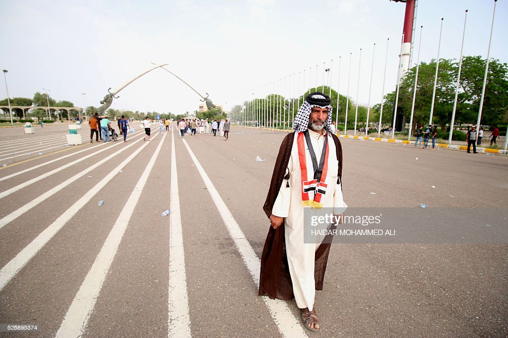 An Iraqi protester walks past the 'Crossed Swords monument' in Baghdad's heavily fortified 'Green Zone' on May 1, 2016, a day after supporters of Shiite cleric Moqtada al-Sadr broke into the area after lawmakers again failed to approve new ministers. Protesters were withdrawing from Baghdad's Green Zone after breaking into the fortified area and storming Iraq's parliament in an unprecedented security breach the day before. The move, which lessens the pressure on politicians in Baghdad, came as rare bombings in the south killed 33 people and wounded dozens. / AFP / HAIDAR