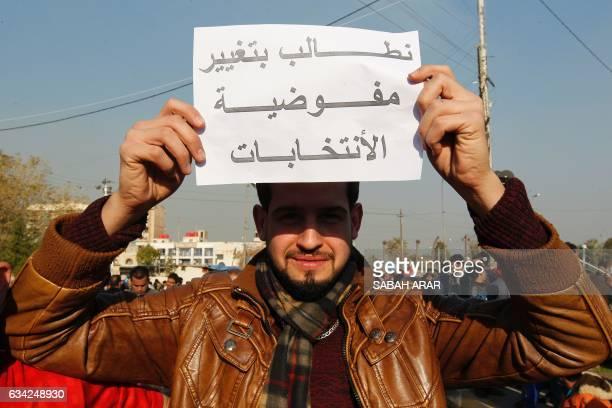 An Iraqi protestor holds a banner reading in Arabic 'We demand to change the electoral commission' as supporters of Iraqi cleric Moqtada alSadr...