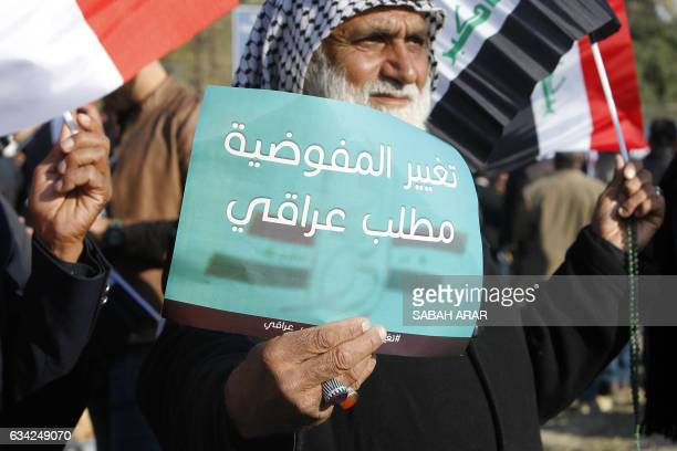 An Iraqi protestor holds a poster reading in Arabic 'Iraqis demand to change the electoral commission' as supporters of Iraqi cleric Moqtada alSadr...
