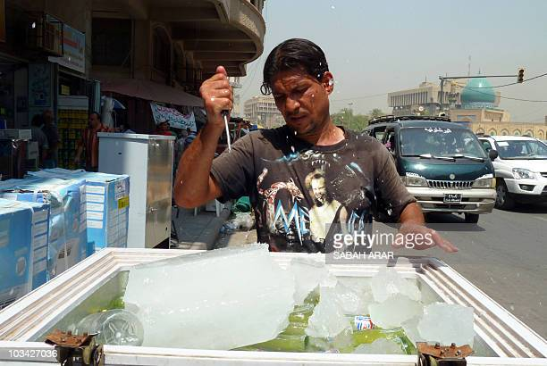 An Iraqi refreshments street vendor breaks an ice block to keep his drinks cool in central Baghdad on August 18 2010 as summer temperatures soared to...