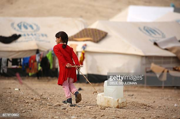 An Iraqi refugee child who fled the Iraqi city of Mosul due to the fighting between government forces' and Islamic State group's jihadists carries...