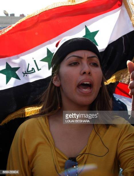 An Iraqi refugee holds a national flag and shout slogans during a protest in the Sayyida Zeinab area south of the Syrian capital Damascus on December...
