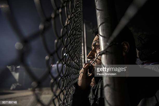 An Iraqi refugee peers through the high fence of a registration area at Moria camp where thousands of refugees wait for days in Lesbos on October...