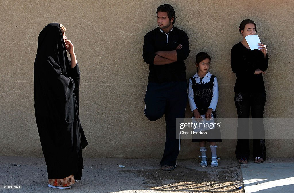 An Iraqi schoolgirl waits with adults outside her school while a US Army patrol passes by in the Baladiyat neighborhood May 15, 2008 in Baghdad, Iraq. 10th Mountain Division soldiers in the area take daily joint patrols with the Iraqi National Police, in the ongoing effort to build up stable national Iraqi security institutions aligned with the national government.