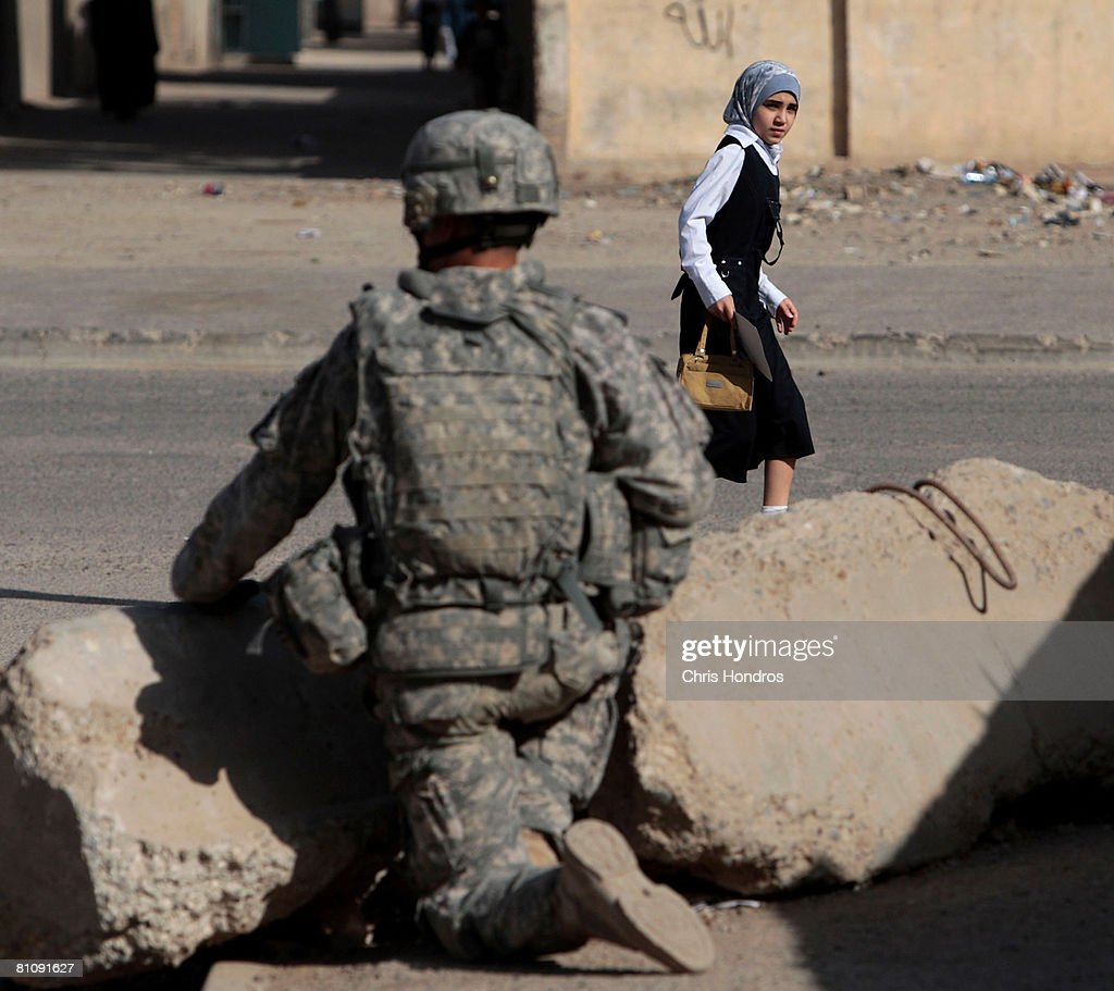 An Iraqi schoolgirl walks past a US Army soldier with the 2nd Battalion, 30th Infantry Regiment holds a defensive position during morning foot patrol in the Baladiyat neighborhood May 15, 2008 in Baghdad, Iraq. 10th Mountain Division soldiers in the area take daily joint patrols with the Iraqi National Police, in the ongoing effort to build up stable national Iraqi security institutions aligned with the national government.