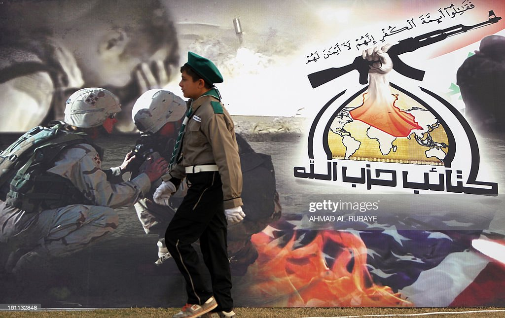 An Iraqi scout walks in front of a poster for the Lebanese Hezbollah Shiite Muslim political party, during celebrations in Baghdad on February 9, 2013, to commemorate the withdrawal of US troops' from Iraq in December 2011, ending nearly nine years of the mainly US led occupation of Iraq.