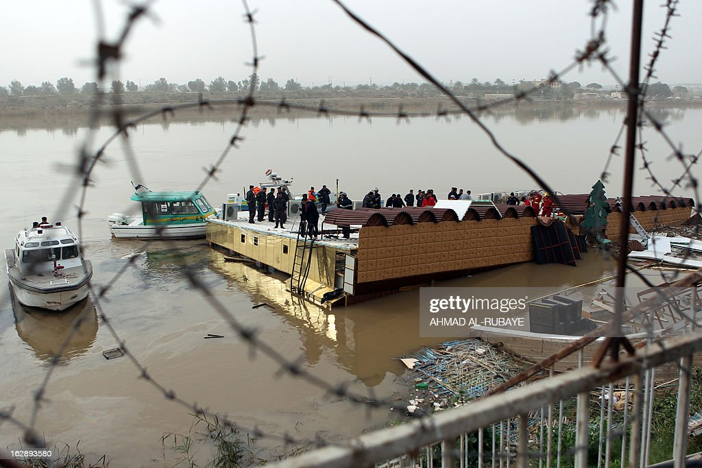 An Iraqi search and rescue team tries to recover the bodies of five people killed on February 28, after the sinking of a floating restaurant belonging to the Lebanese Club in Baghdad, on March 1, 2013. A floating restaurant moored on the bank of Baghdad's Tigris River sank on February 28, during a private party with 150 people on board, leaving five people dead, Iraqi officials said. AFP PHOTO/AHMAD AL-RUBAYE
