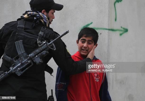 TOPSHOT An Iraqi security forces member comforts a boy in AlRisala neighbourhood on March 22 following a mortar shell attack by Islamic State...