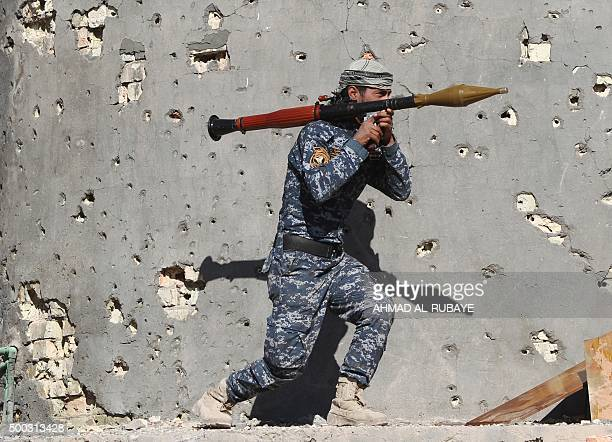TOPSHOT An Iraqi security forces member takes combat position as he carries a Rocket Propelled Grenade in the rural town of Husayba in the Euphrates...