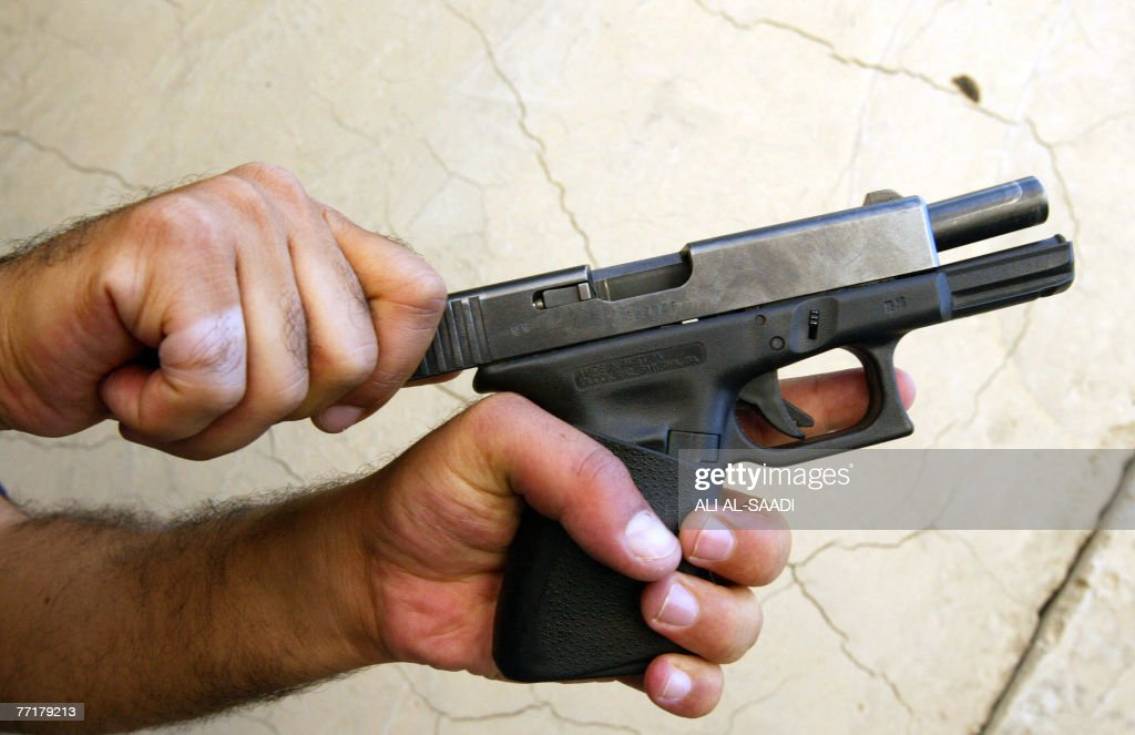 An Iraqi security guard poses with an Austrianmade Glock 9mm semiautomatic pistol in Baghdad 04 October 2007 US authorities have launched an inquiry...