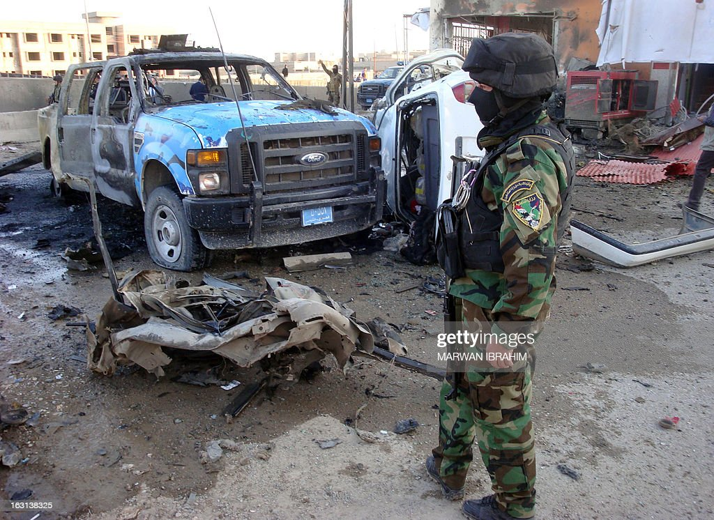 An Iraqi security office stands close to the debris following a car bomb, in the northern city of Kirkuk on March 5, 2013. Two car bombs targeted police in the northern city of Kirkuk, killing five and wounding at least 18, while gunmen killed a town council member and a North Oil Company employee south of the city, police and a health official said. AFP PHOTO/MARWAN IBRAHIM