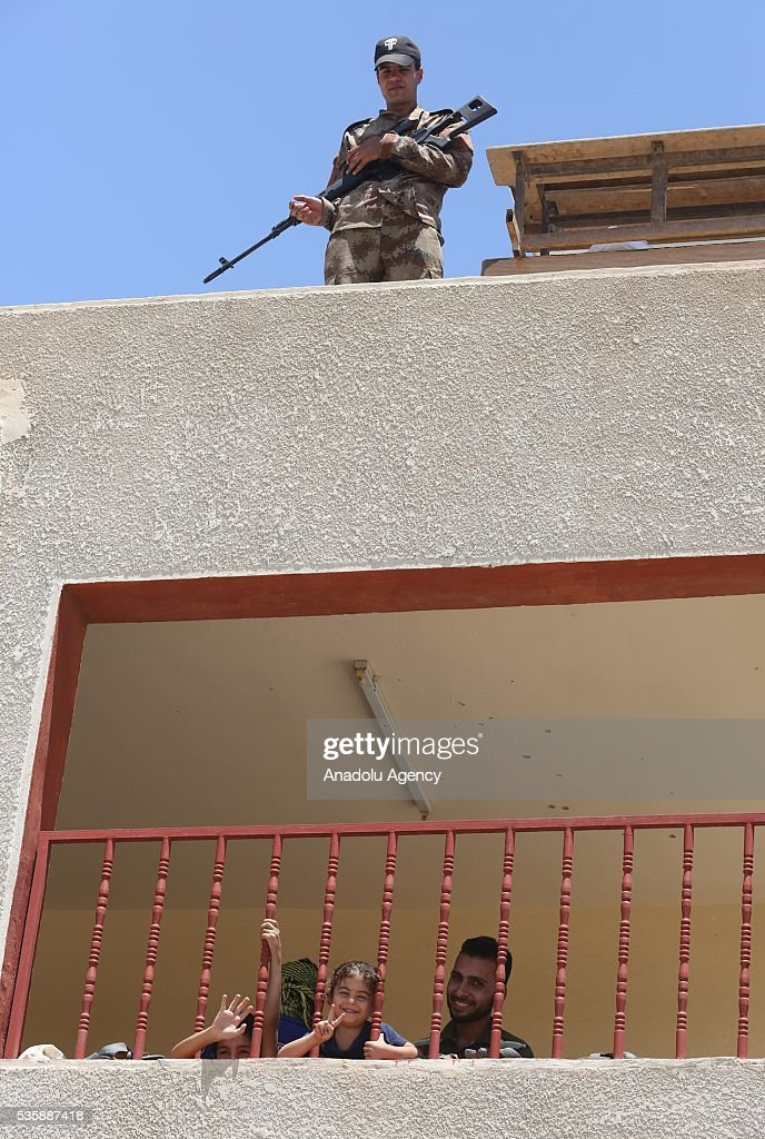 An Iraqi security soldier stands guard on the roof as Iraqi people in Fallujah town leave their home due to conflicts between Daesh and security forces in Anbar, Iraq on May 30, 2016. Some of the families who left their home are placed in a school in Karma Town, west of Anbar city.
