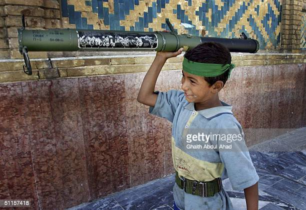 An Iraqi Shiite boy plays with a US antitank missile launcher captured by militia men loyal to the radical cleric Moqtada alSadr during heavy...