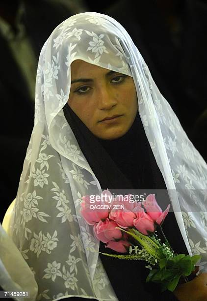 An Iraqi Shiite bride takes part in a mass wedding in the holy city of Najaf 16 July 2006 550 couples were married today during a mass wedding...